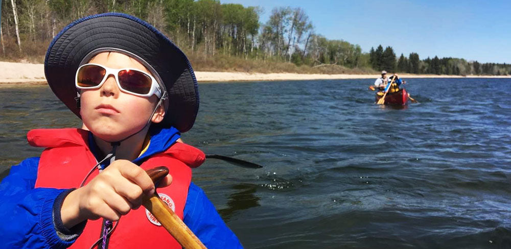 Child paddling canoe wearing sunglasses