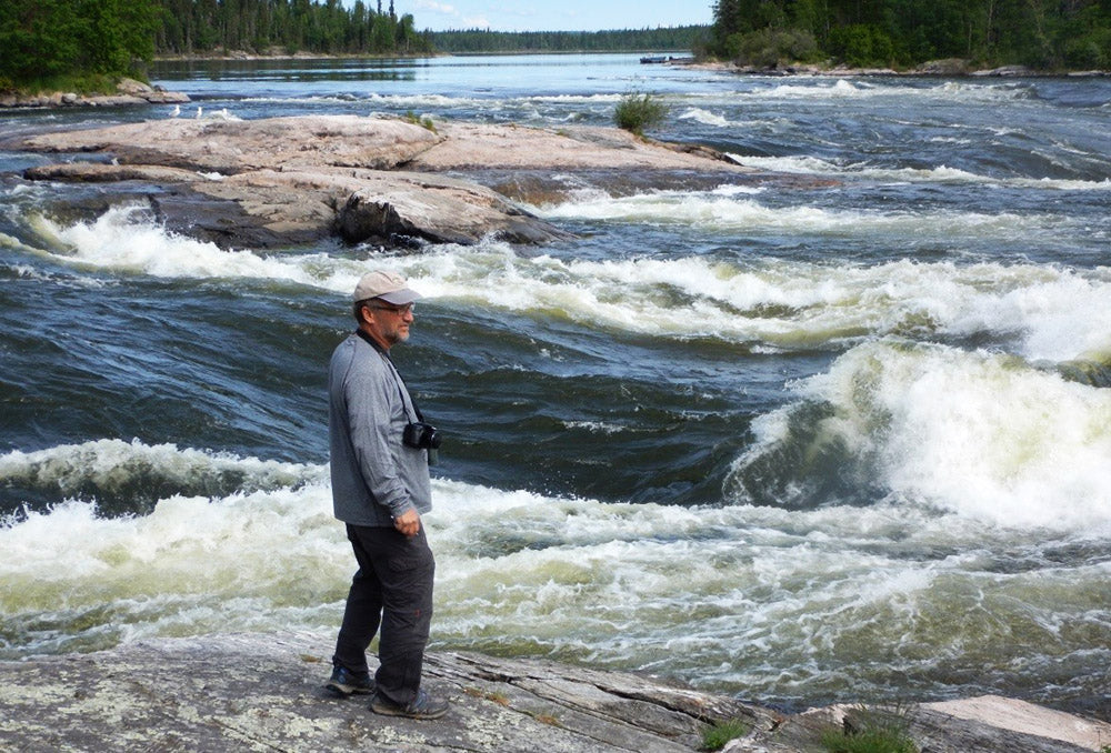 a paddler scouting rapids on the Churchill River