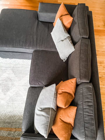 Sofa styled with Orange and charcoal cushions