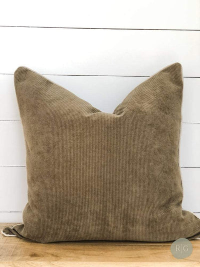 Corduroy khaki cushion against white wall