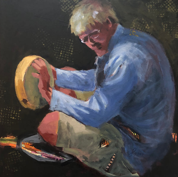 A man with blonde hair and glasses, wearing a long sleeved blue shirt, taps out a rhythm on a hand drum.