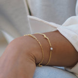 Close up of two gold bracelets