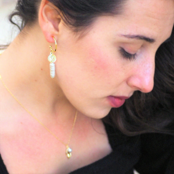Woman wearing drop pearl earrings