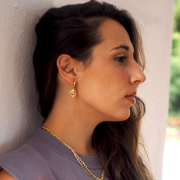 Model with gold eye coin huggie earrings and double necklace