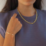 Woman with an eagle bracelet and a doble essential necklace