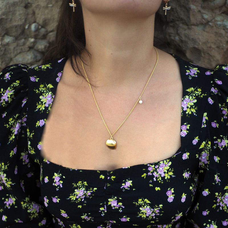 Woman wearing a gold shell necklace and dragon fly earrings