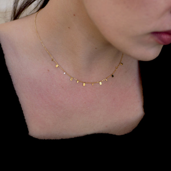 Close up photo of a woman with Golden squares necklace
