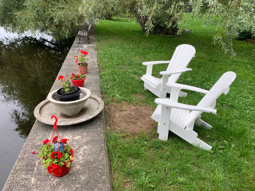 Plastic Adirondack chairs next to a river