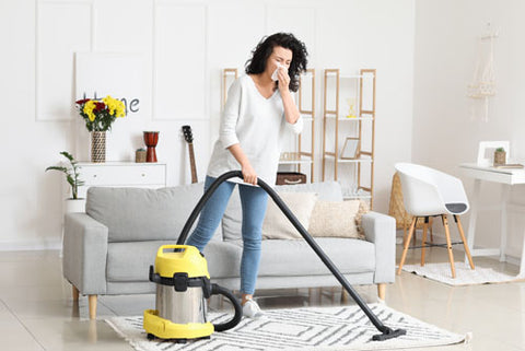 Women cleaning house for Chinese New Year with dust allergy sneezing as she vacuum the house