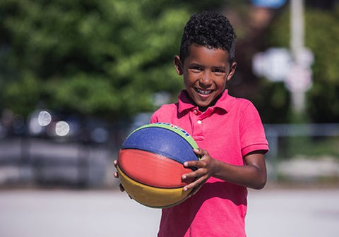 Self-confident child playing ball outdoors