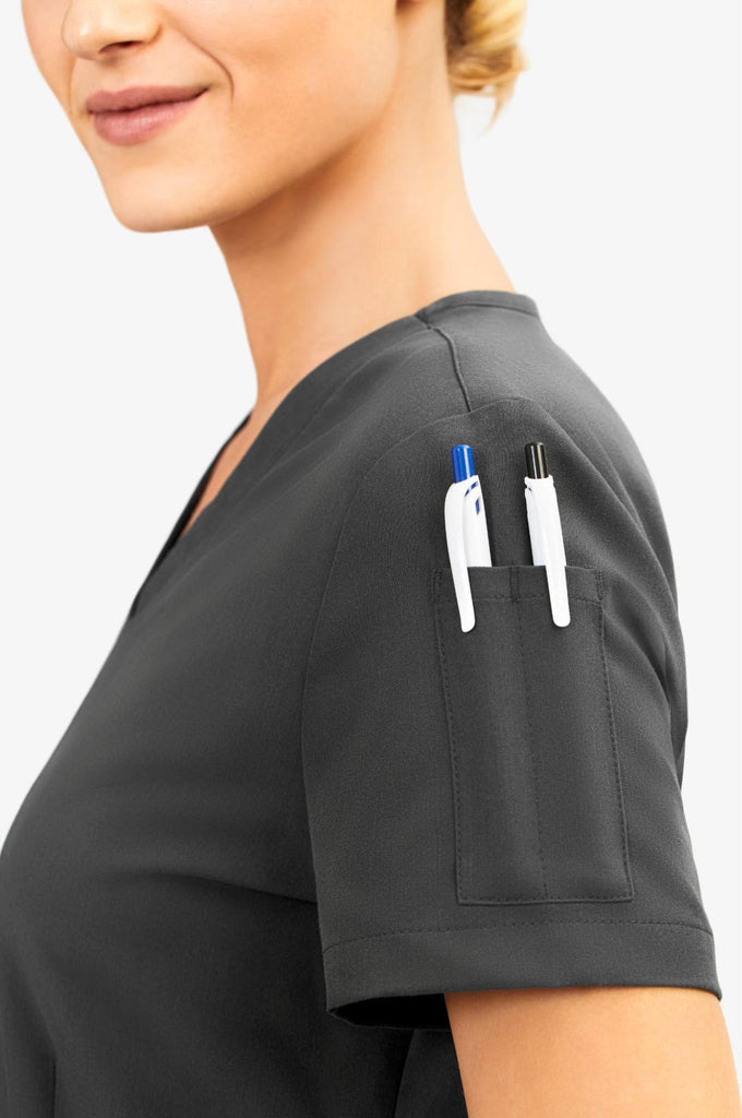 Woman wearing scrubs with pen pockets on the sleeve