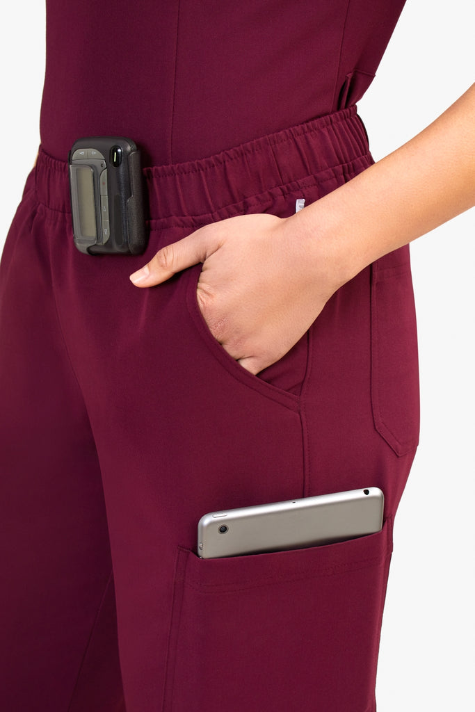 best scrubs for curvy women: Woman wearing scrubs with her hand in her pocket, a tablet inside another and a pager clipped on the waistband