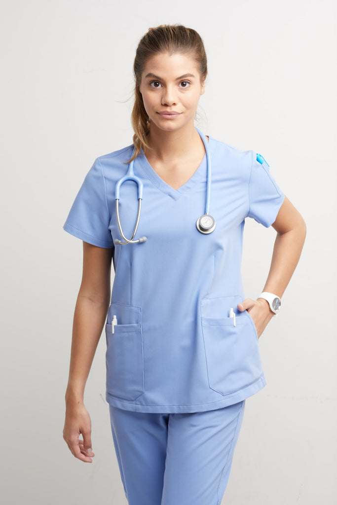 A woman poses while wearing veterinary scrubs.