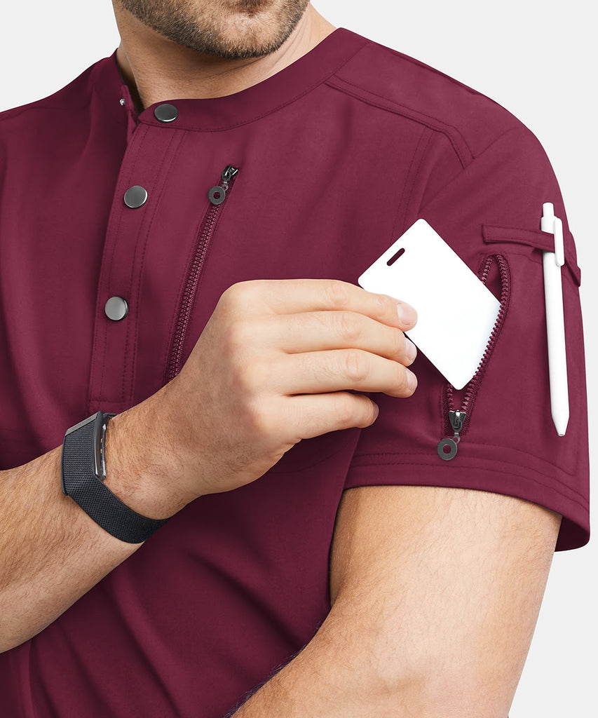 A man puts a card inside his veterinary scrubs pocket.