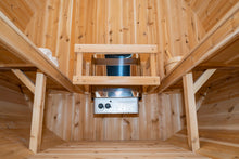 Load image into Gallery viewer, Camera view from the bottom of the floor inside the Dundalk Leisurecraft Canadian Timber Harmony Barrel Sauna viewing 6KW heater, towels on the left, benches on the left and right, and water bucket with ladle on the right