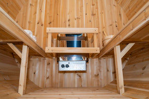 Camera view from the bottom of the floor inside the Dundalk Leisurecraft Canadian Timber Harmony Barrel Sauna viewing 6KW heater, towels on the left, benches on the left and right, and water bucket with ladle on the right