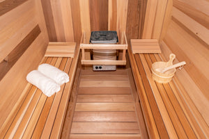 Inside the Dundalk Leisurecraft Tranquility Barrel Sauna viewing the 6KW Heater, water bucket with ladle and towels