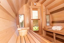 Load image into Gallery viewer, Inside the Dundalk Leisurecraft Tranquility Barrel Sauna, looking outside through the door's window, viewing towels and water bucket with ladle