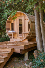 Load image into Gallery viewer, Dundalk Leisurecraft Canadian Timber Tranquility Barrel Sauna with Front Porch, placed outside near trees in a backyard facing left