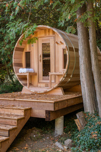 Dundalk Leisurecraft Canadian Timber Tranquility Barrel Sauna with Front Porch, placed outside near trees in a backyard facing left