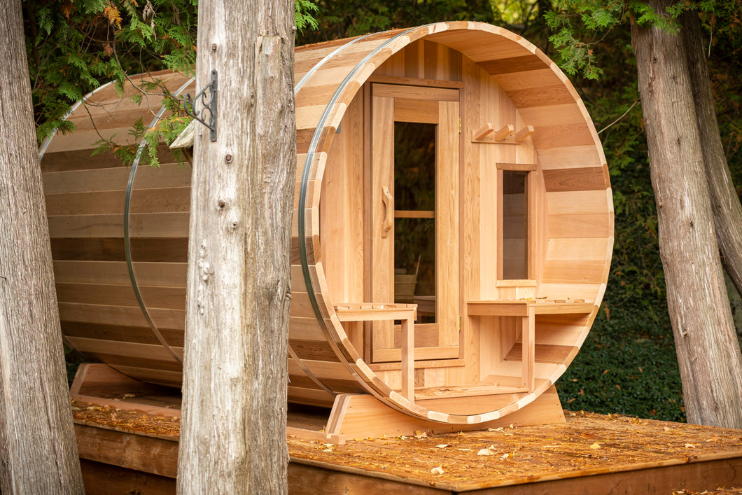 Dundalk Leisurecraft Canadian Timber Tranquility Barrel Sauna with Front Porch, placed outside near trees in a backyard facing right