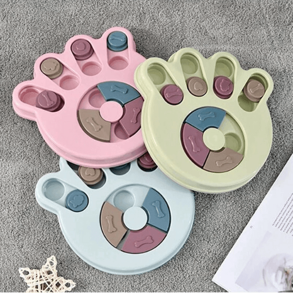 Three Dog Puzzle Feeder in paw shape, one in green, one in blue and one in pink. Each paw feeder has 7 compartments where treats can be hid.