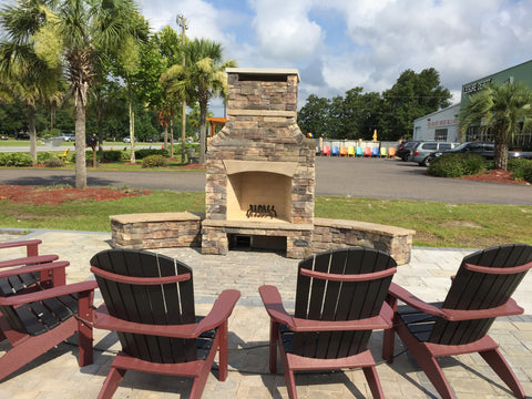 Outdoor fireplace with built in benches and fan back poly chairs