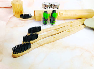 Four eco-friendly charcoal bamboo toothbrushes and two bottles of charcoal bamboo floss.