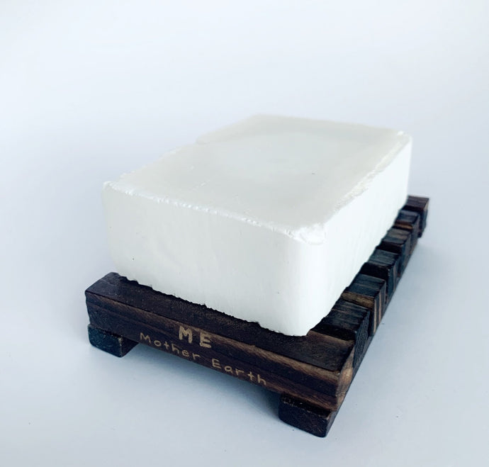 Sustainable bamboo soap dish with soap sitting on top.