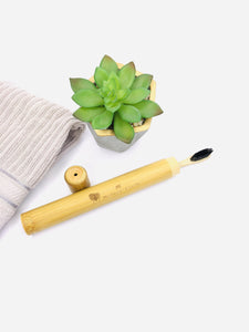 All-natural bamboo toothbrush travel case with charcoal bamboo toothbrush inside.