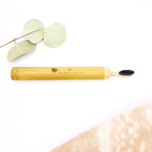 Eco-friendly bamboo toothbrush travel case with charcoal bamboo toothbrush inside.