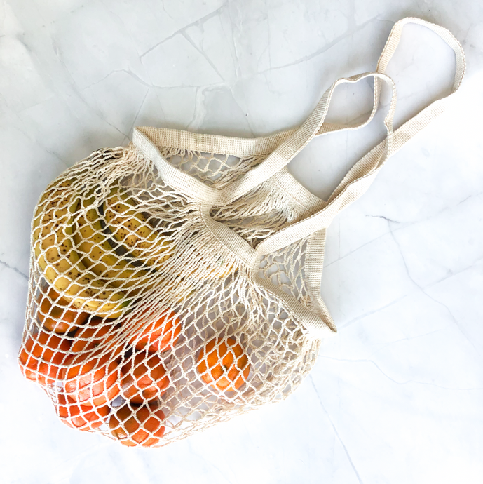 Reusable eco-friendly 100% cotton mesh grocery tote with two apples and two oranges in it.