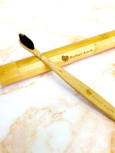 Load image into Gallery viewer, All-natural charcoal bamboo toothbrush laying across a bamboo toothbrush travel case.