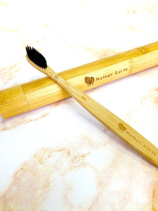 All-natural charcoal bamboo toothbrush laying across a bamboo toothbrush travel case.