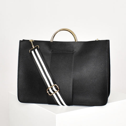 Black vegan leather tote with gold metal handles and detachable black and white strap