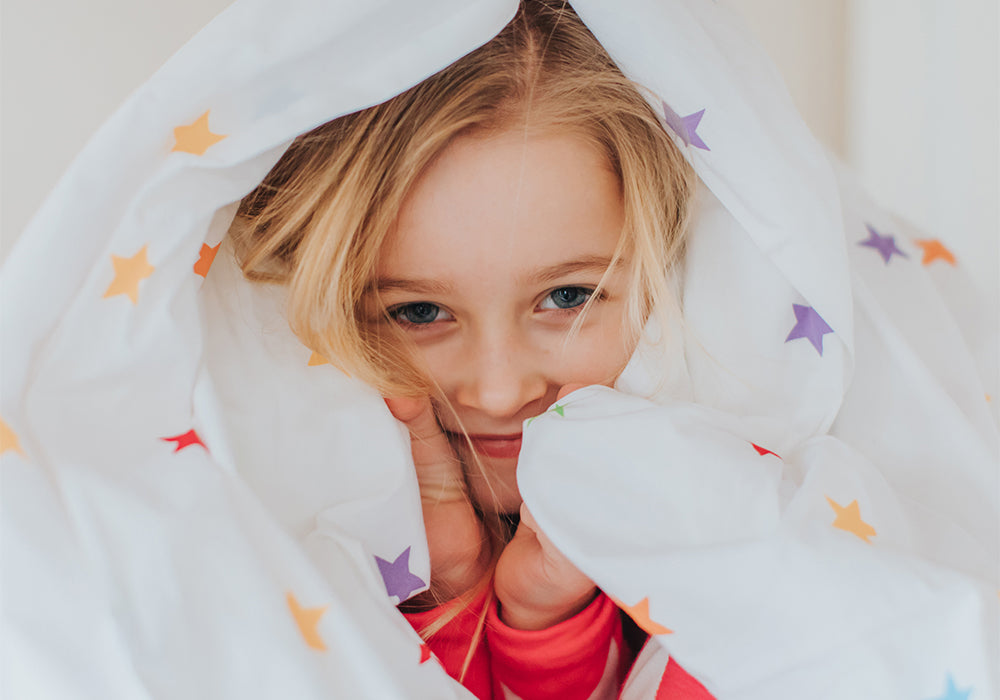 Child Wrapped in Duvet Looking at Camera