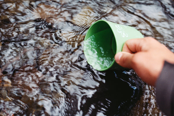 hand filling cup from stream