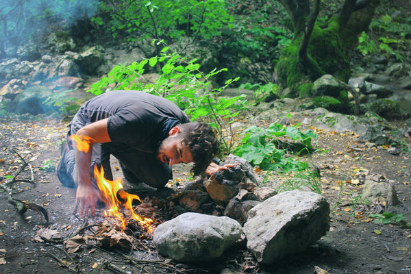 man blowing on campfire