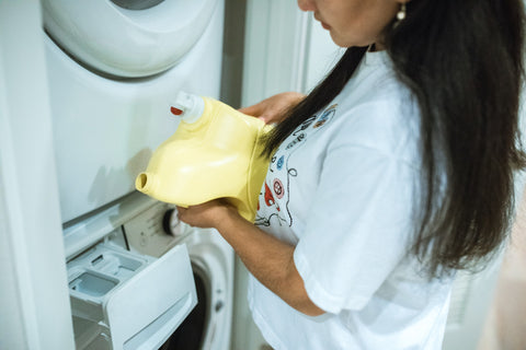 woman pouring laundry detergent into washer