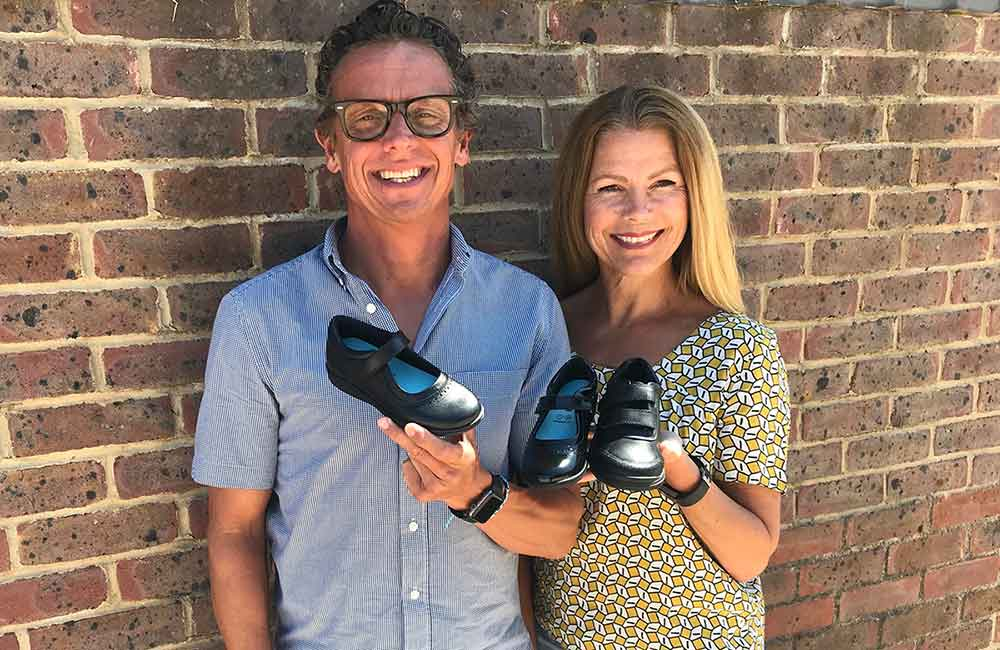 Lincoln and Sharon New holding up their sole buddy shoe collection