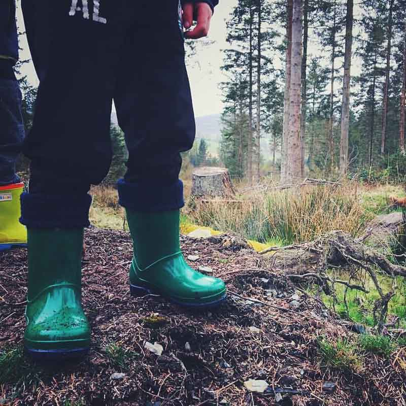 Green kids wellies being worn in the forest by term footwear