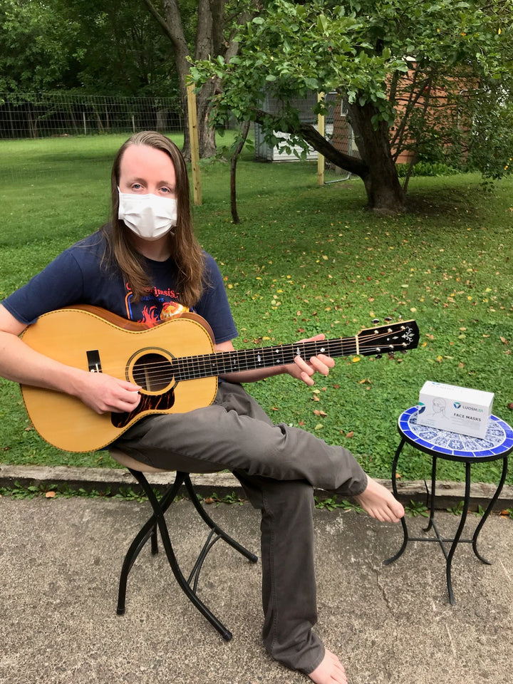 "Michele DeMarre wearing a Luosh face mask while playing a guitar.  He comments, ""Good quality, safe and pleasantly breathable.  Ordered 8/15, arrived 8/17 via US Post Office.  Box has several masks packaged together within box, which we liked..."""