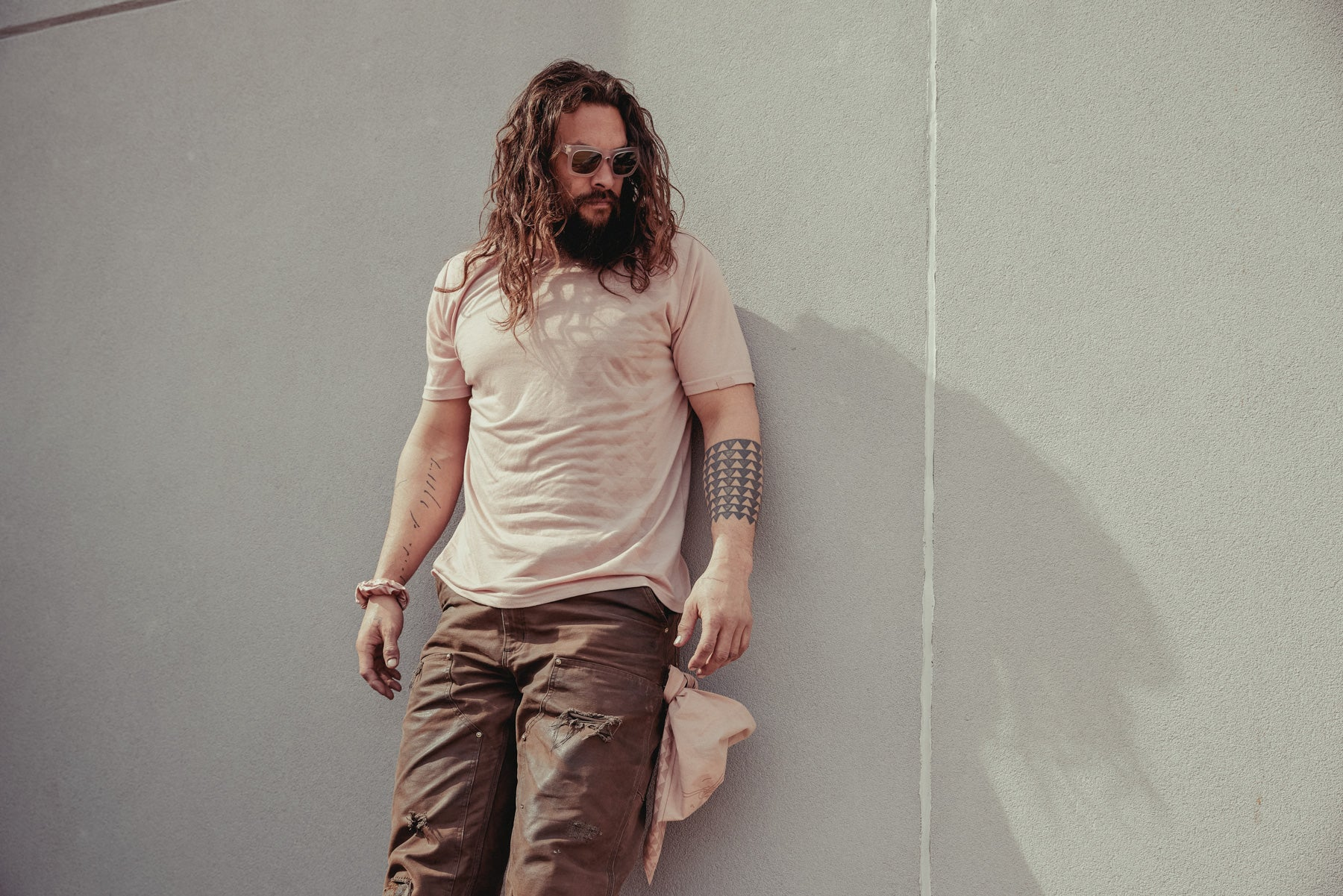 Jason Momoa shown wearing the so ill x on the roam dirty pink nokoa tee leaning up against a wall