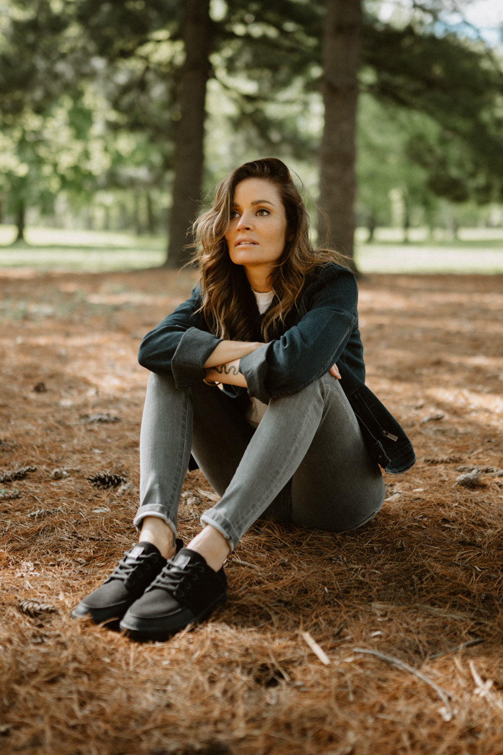 a woman wears the so ill smoke wash out denim in a wooded area