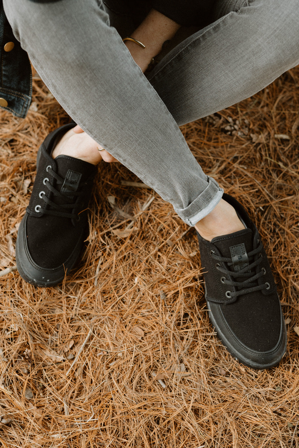 a close shot of the so ill smoke wash out women's denim in a forested area