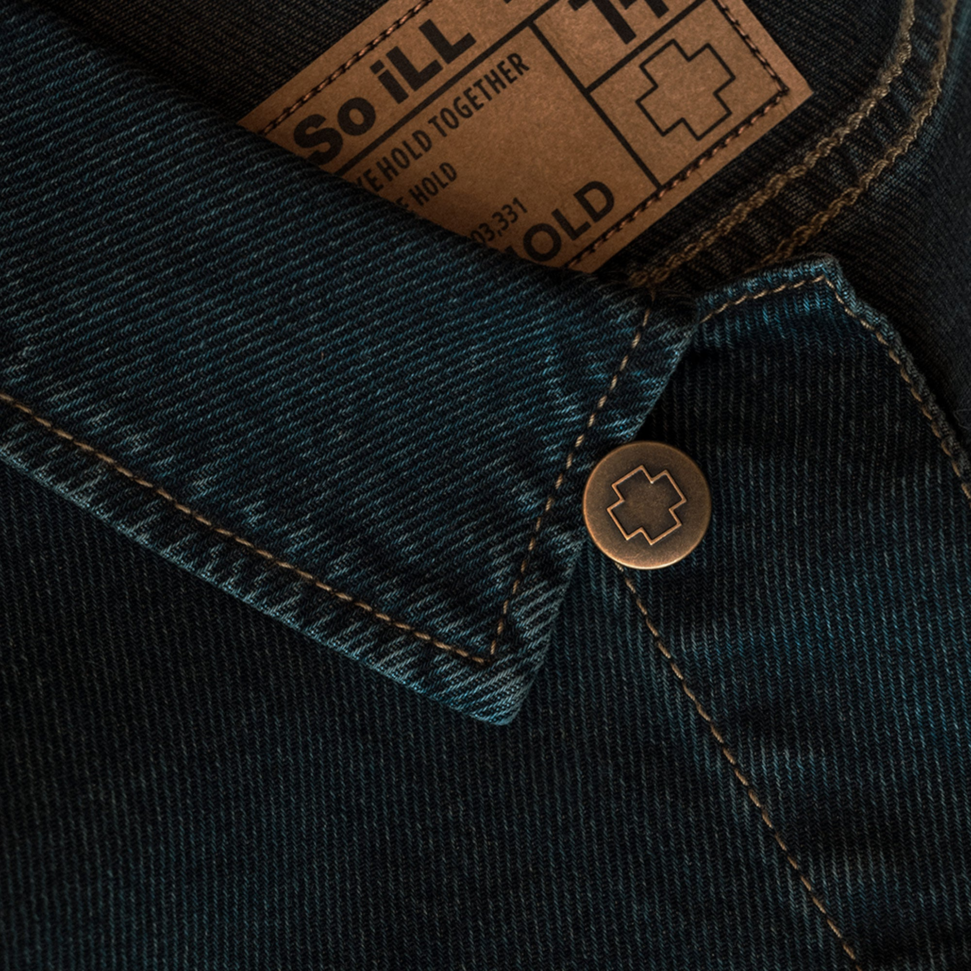 a close shot of the tag and emblazoned button the so ill unisex denim jacket