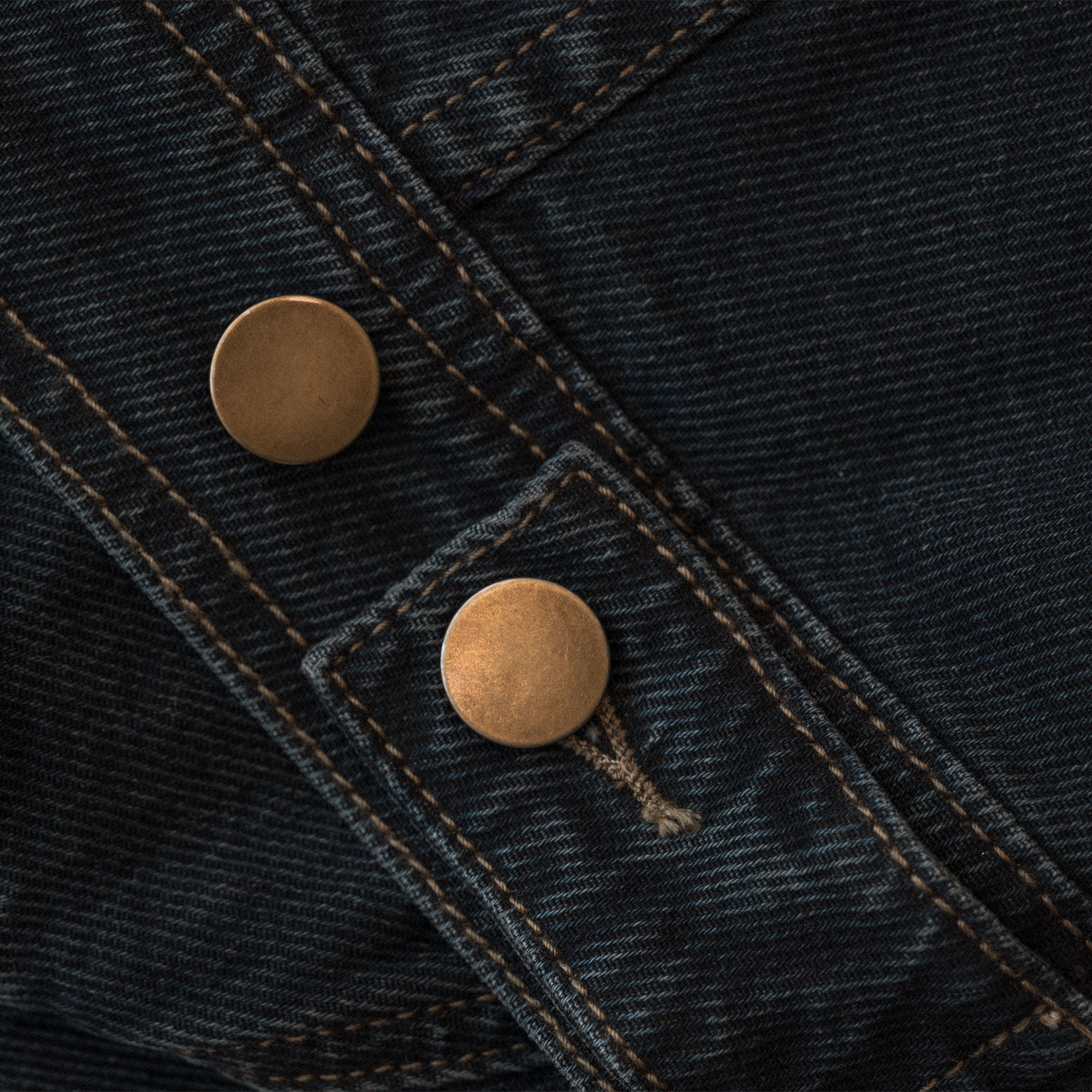 a close shot of the metal buttons on the so ill unisex denim jacket