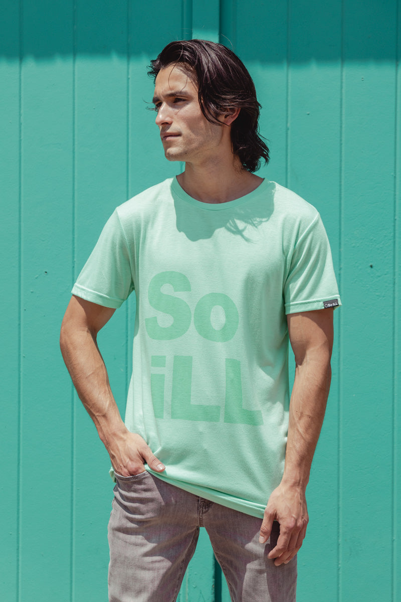 A man wears the seafoam colored stacked logo tee in front of a teal door