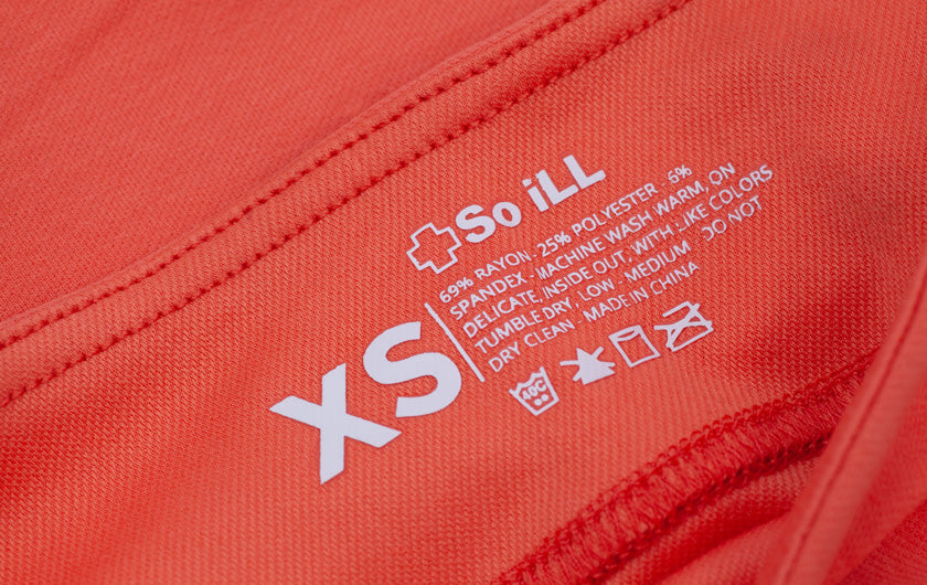 close up shot of tag of Coral Colored So iLL Active Jeans