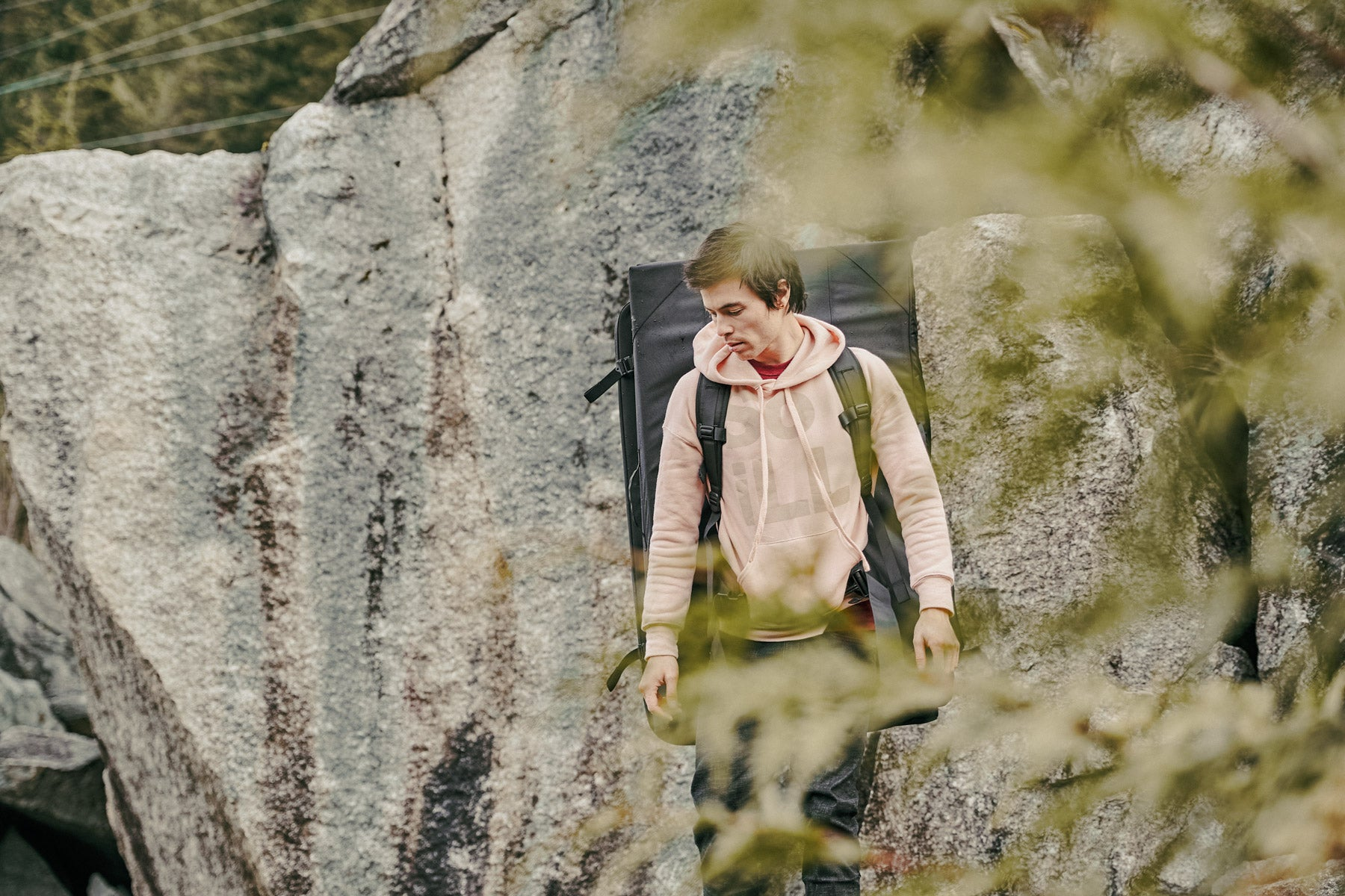 a man in the mountains carrying a climbing crash pad wearing a pink so ill hoodie